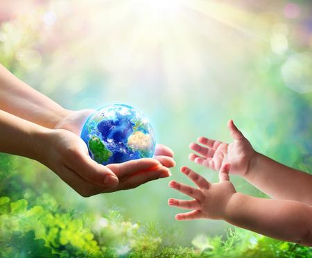 Mutter gibt blaue Erde in die Hände der Tochter