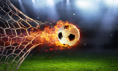 Balón de fútbol ardiente en meta con red en llamas Foto de archivo