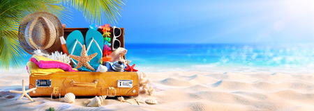 Full Suitcase With Accessories On Tropical Beach Archivio Fotografico - 123144515