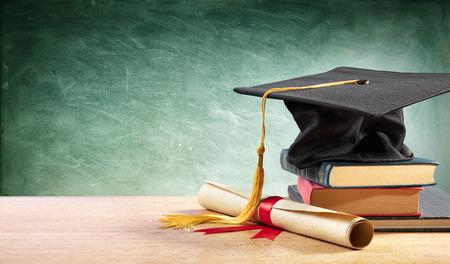Afstudeerpet en diploma op tafel met boeken Stockfoto