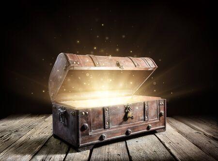 Cofre del tesoro: baúl antiguo abierto con luces mágicas brillantes en la oscuridad