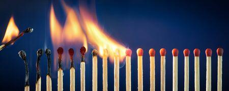Fiammiferi accesi in fila che bruciano in una reazione a catena