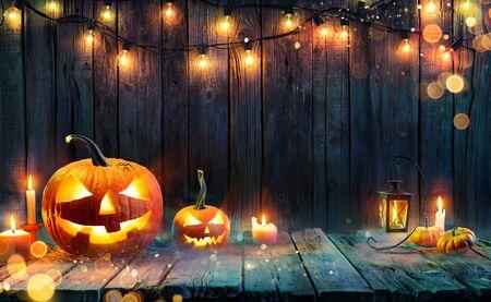 Halloween - Jack O 'Lanterns - Velas y luces de cadena en la mesa de madera