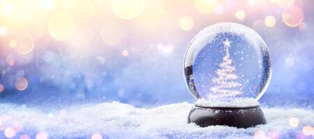 Shiny Christmas Tree In Snow Globe On Snow With Golden Lights 免版税图像