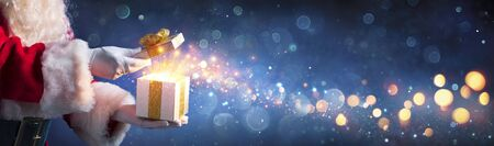 Santa Claus Opening Christmas Present With Golden Stars In Night Banco de Imagens