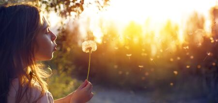 Little Girl Blowing Dandelion Flower At Sunset Imagens