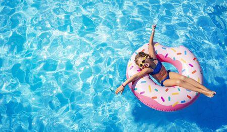 Enfant drôle sur le beignet gonflable dans la piscine