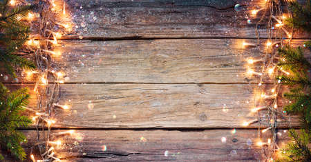 Rustic Christmas Border - Fir Branches And String Light On Old Wooden Plank With Defocused Abstract Bokeh Stok Fotoğraf