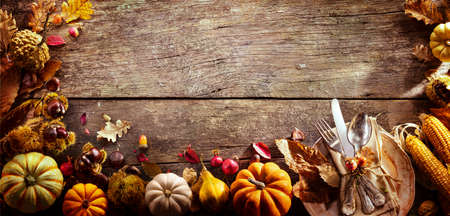 Thanksgiving - Table Setting With Silverware And Autumnal Decoration On Aged Wooden Plank