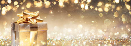 Golden Gift Box On Glitter In Abstract Background With Defocused Lights Stok Fotoğraf