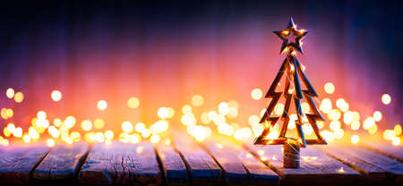 Christmas Light And Wooden Tree On Table With Defocused Rustic Background