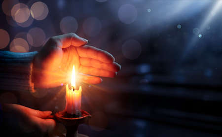 Defocused Hope Concept - Hands Holding Candle With Shining Flame And Blurry Lights