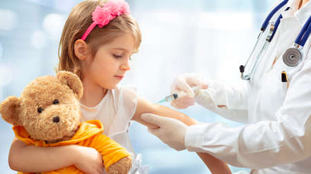 Vaccination Concept - Female Doctor Vaccinating Cute Little Girl On Blue Background