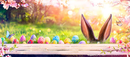 Abstract Defocused Easter Table - Ears Bunny Behind Grass And Decorated Eggs In Flowery Field