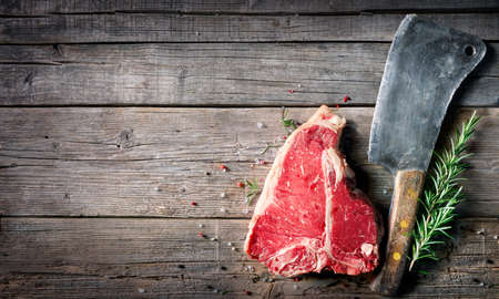T-bone beef steak - Raw meat for grill with fresh herbs and cleaver 写真素材