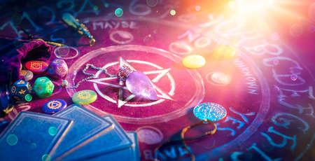 Cartomancy And Tarot - Pendulum On Altar With Defocused Cards And Chakra Stones