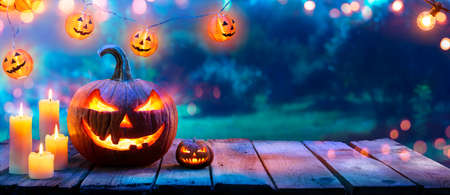 Pumpkin With Candles On Table In Garden - Halloween In Outdoor 写真素材