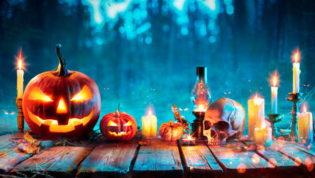 Halloween At Night - Jack O Lantern On Table With Candles In Forest