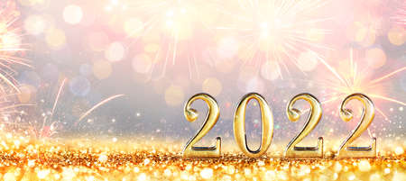 2022 New Year Celebration - Golden Numbers On Glitter With Fireworks And Defocused Background 写真素材