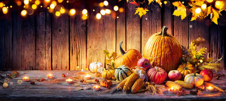 Thanksgiving Celebration - Pumpkins On Rustic Table With Corncobs And Apples With Ears Wheat