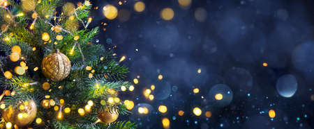 Christmas Tree In Blue Night - Golden Balls On Fir Branches With Defocused Lights In Abstract Background