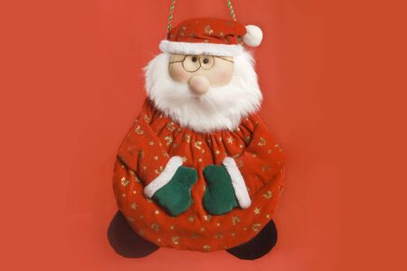 glove puppet: christmas hanging doll. santa claus. red backgound. horizontal image.  Stock Photo