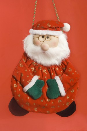 glove puppet: santa claus puppet. cristmas ornamient. red background. vertical image. Stock Photo