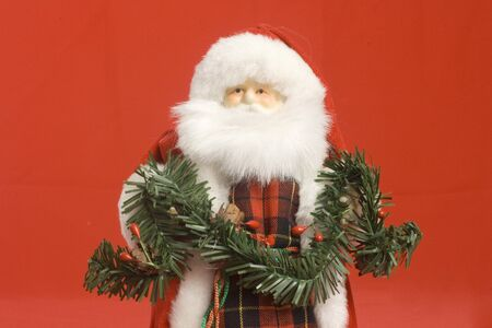 santa claus image with green garland in his hands. horizontal image with red background. photo