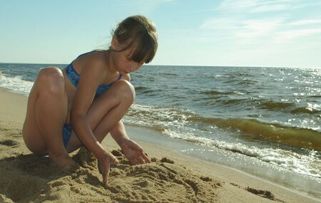 young girl in blue bathing suit and sea sand Stock Photo - 7476918