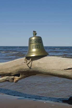 titanic: ship bell of Titanic ship on log