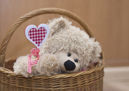 teddy bear holding  heart in  basket Valenyines day gift photo