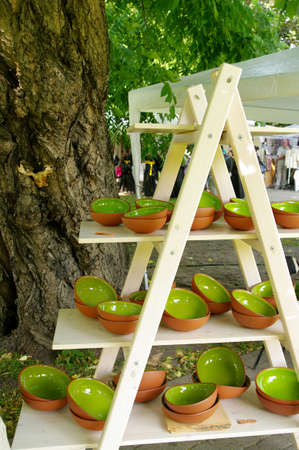 artisans: green clay pottery plates on wooden stans at the fair of artisans in Riga