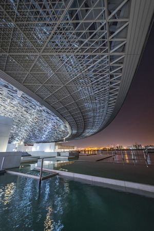 Louvre, Abu Dhabi, United Arab Emirates - Dec.29, 2017: Pools of the museum at night under the wing of dome with a view of the city lights