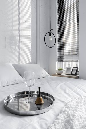 White bedroom interior with a wine glass on a tray on the bed Imagens