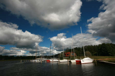 descriptive: Boats on Lake in Cloudy Weather Stock Photo