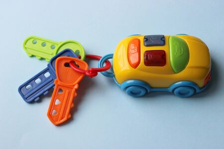 Children`s toy car with keys. Toy keychain from the car. Multi-colored key with keychain. The hook from the toy car is isolated on a blue background.