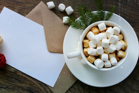 Cup with homemade Christmas hot chocolate drink, marshmallows and holiday greeting card on wooden background. Copy space. Winter time concept. Flat position, top view.