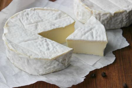 Camembert cheese. Farm products, cottage cheese. round head cheese with mold, sliced on a wooden Board surrounded by fragrant spices. Gourmet cheese plate.