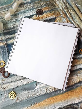 Photo of notepad against the background of a relief wall with decorative elements 免版税图像