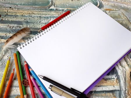 notepad for the sketch on a colourful background with a pencils 免版税图像