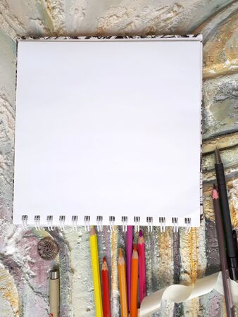 Photo of notepad against the background of a relief wall with color pencils and other decorative elements