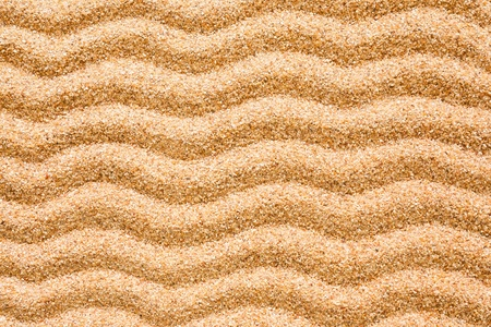 denote: A series of wave patterns set on beach sand  This can be used as a background to denote beach, summer etc