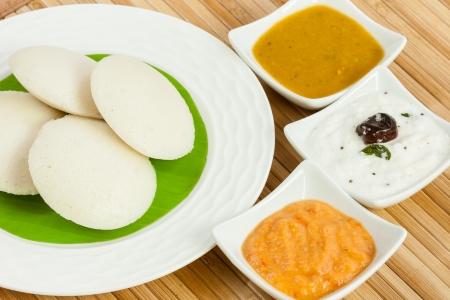 chutney: Un tradicional del sur desayuno indio �tnico Ociosamente pastel de arroz Idli servido con chutney de tomate, chutney de coco y sambar en un plato cubierto con hoja de pl�tano