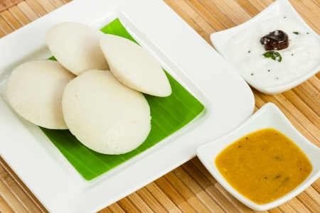 A traditional ethnic south Indian breakfast of Idly  Idli   rice cake  served with coconut chutney and sambar on a plate lined with banana leaf  photo