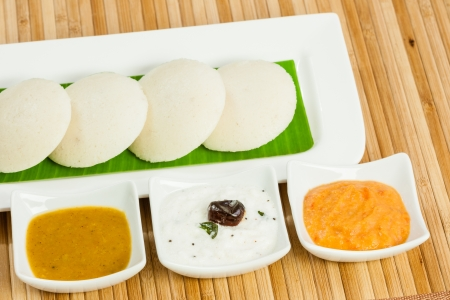 A traditional ethnic south Indian breakfast of Idly  Idli   rice cake  served with its condiments  tomato chutney, coconut chutney and sambar  on a plate lined with banana leaf  photo