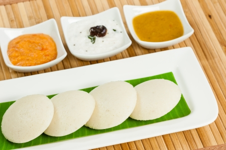 chutney: A traditional ethnic south Indian breakfast of Idly  Idli   rice cake  served with its condiments  tomato chutney, coconut chutney and sambar  on a plate lined with banana leaf  Stock Photo