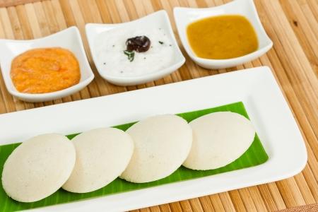 banana leaf: Un tradicional del sur desayuno indio �tnico Ociosamente pastel de arroz Idli servido con condimentos de su chutney de tomate, chutney de coco y sambar en un plato cubierto con hoja de pl�tano Foto de archivo