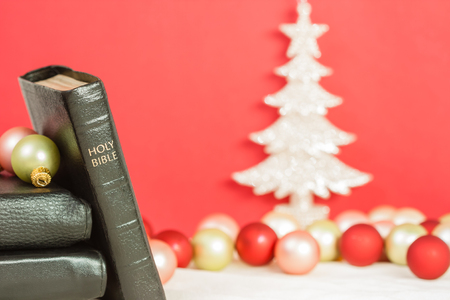 sharply: A sharply focused Holy Bible with Christmas tree and ornaments Stock Photo