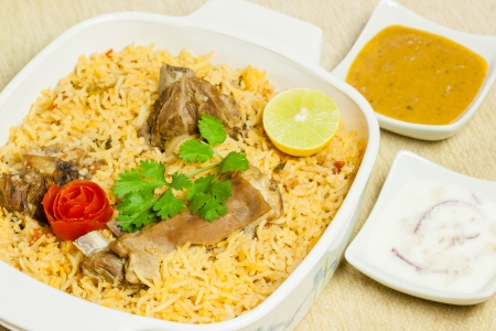 mutton: Closeup view of delicious mutton  lamb  biryani garnished with tomato peel, cilantro and lemon  It is served with its condiments onion salad  raita  and vegetable curry