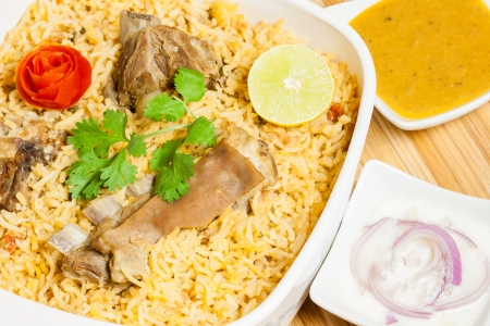 mutton: Closeup view from the top of delicious mutton  lamb  biryani garnished with tomato peel, cilantro and lemon  It is served with onion salad  raita  and vegetable curry